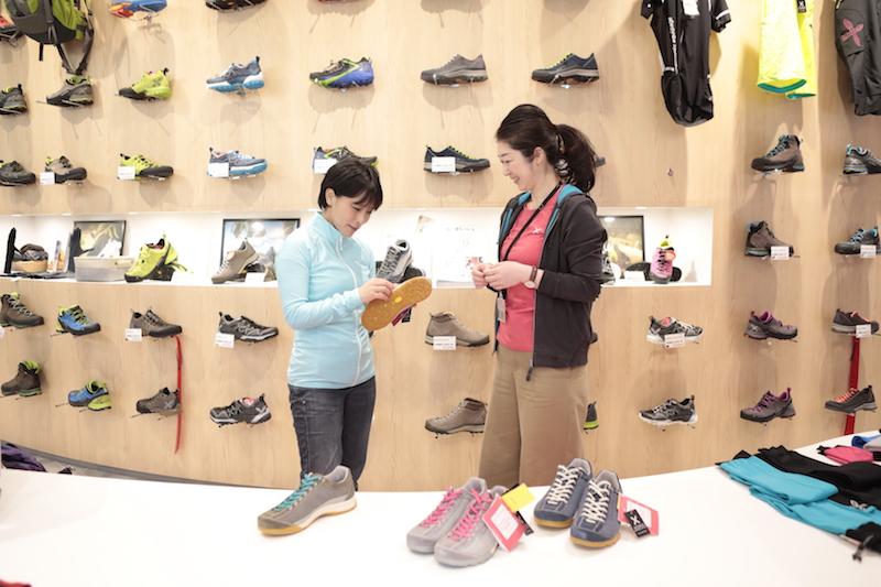 靴を見る小林千穂さんと店長