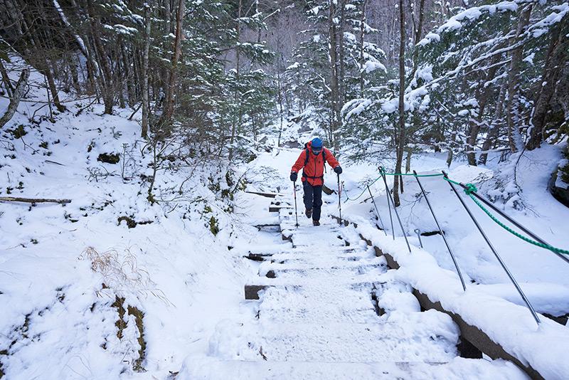 雪が積もった登山道を歩く